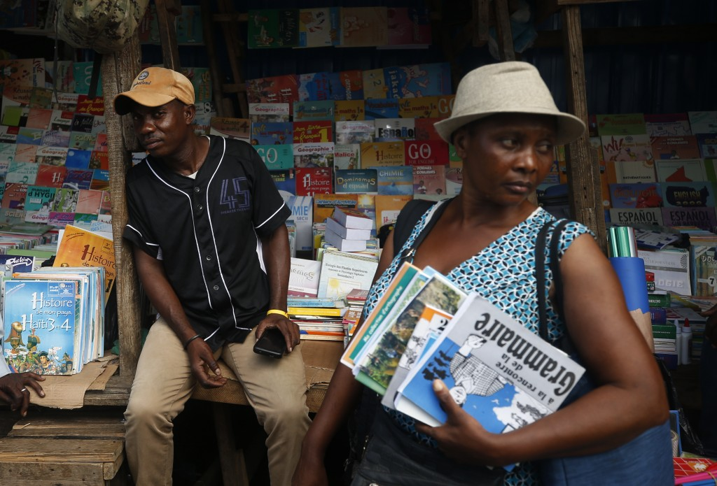 Marcel Cineus, left, keeps an eye on a customer browsing his book stand at a market in Petionville, Port-au-Prince, Haiti, Wednesday, Oct. 2, 2019. Sc...