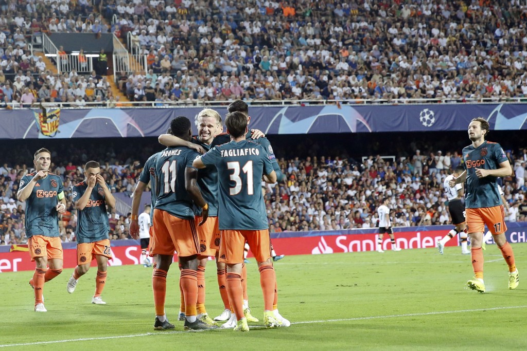 Ajax's Quincy Promes is congratulated by teammates after scoring during the Champions League group H soccer match between Valencia and Ajax, at the Me...