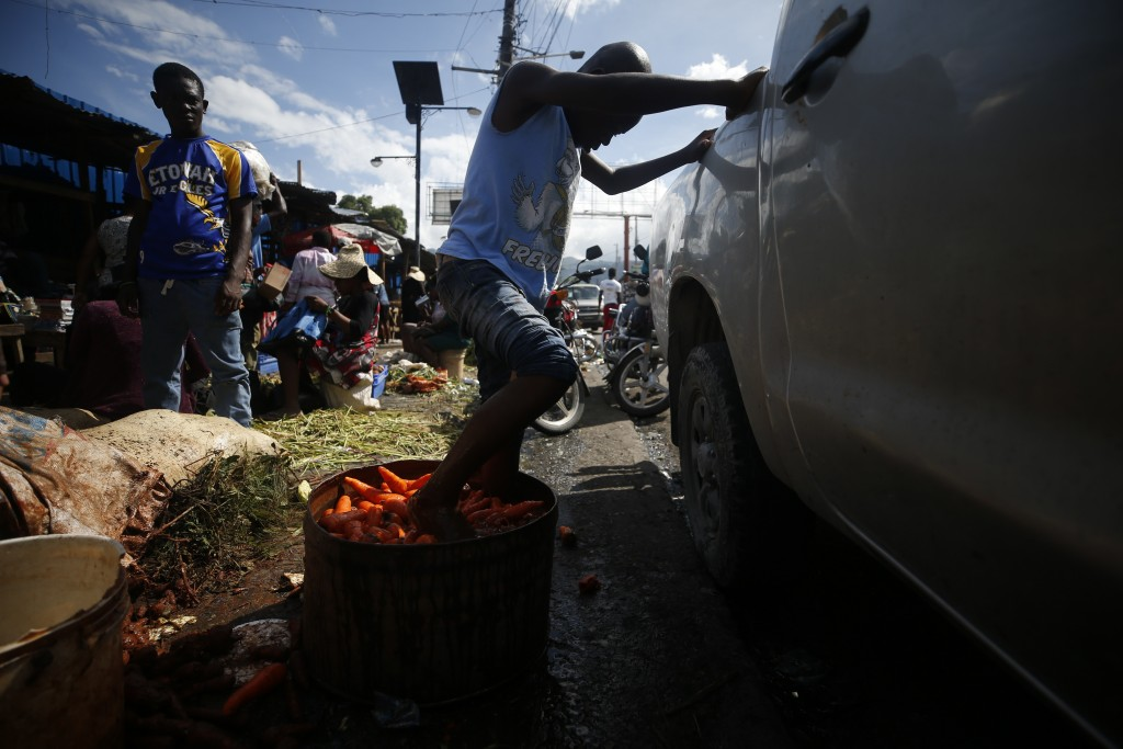 A youth cleans carrots by agitating them with his feet in a tub of murky water, at a market in Petionville, Port-au-Prince, Haiti, Wednesday, Oct. 2, ...