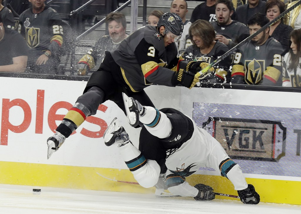 Vegas Golden Knights defenseman Brayden McNabb leaps over San Jose Sharks center Tomas Hertl during the first period of an NHL hockey game Wednesday, ...