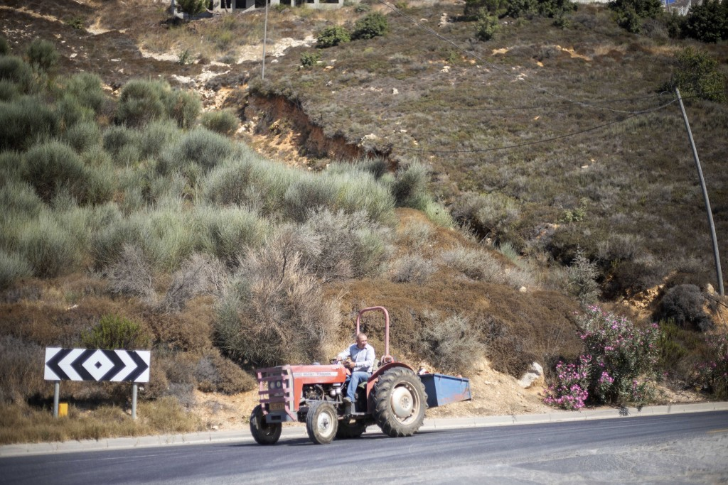 In this Sept. 10 2019 photo, a Druze farmer drives his tractor in the Israeli-controlled Golan Heights near the border with Syria. Towering wind turbi...