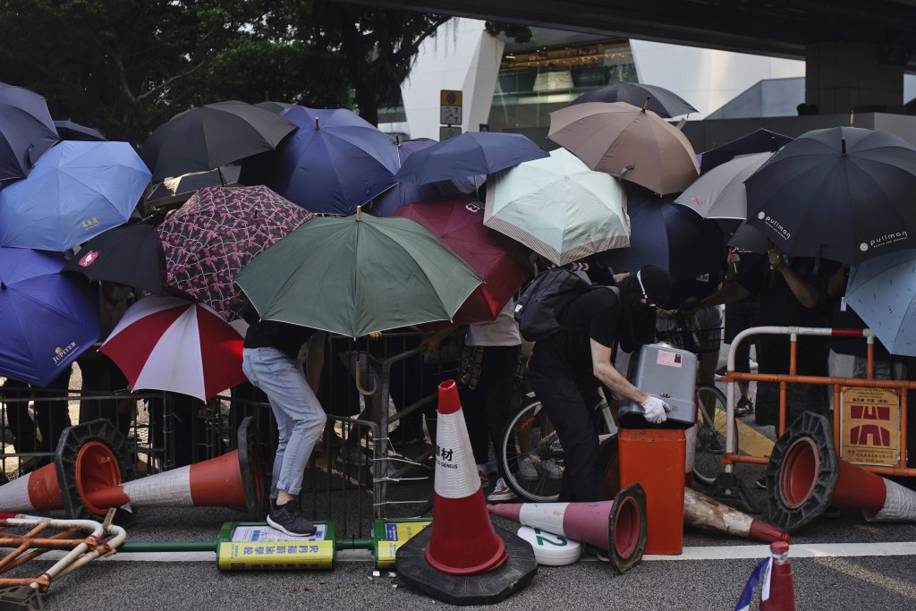 Protesters hide behind umbrellas as they form a barricade to block a road in Hong Kong on Friday, Oct. 4, 2019. Thousands of protesters in masks are s...