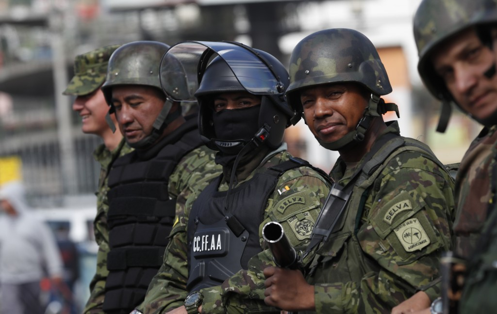 Soldiers guard an intersection after a day of rioting in Quito, Ecuador, Friday, Oct. 4, 2019. Ecuador's president has declared a state of emergency t