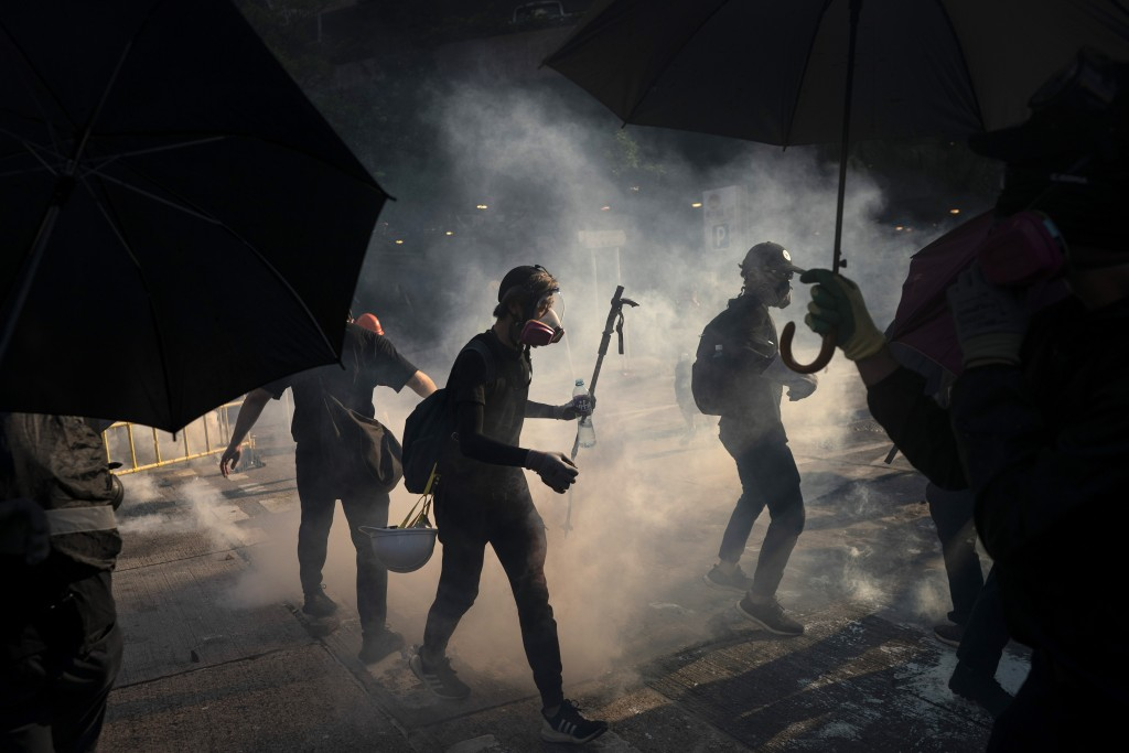 In this Tuesday, Oct. 1, 2019, file photo, black-clad protestors stand surrounded by smoke from tear gas shells in Hong Kong. Hong Kong police shot a ...