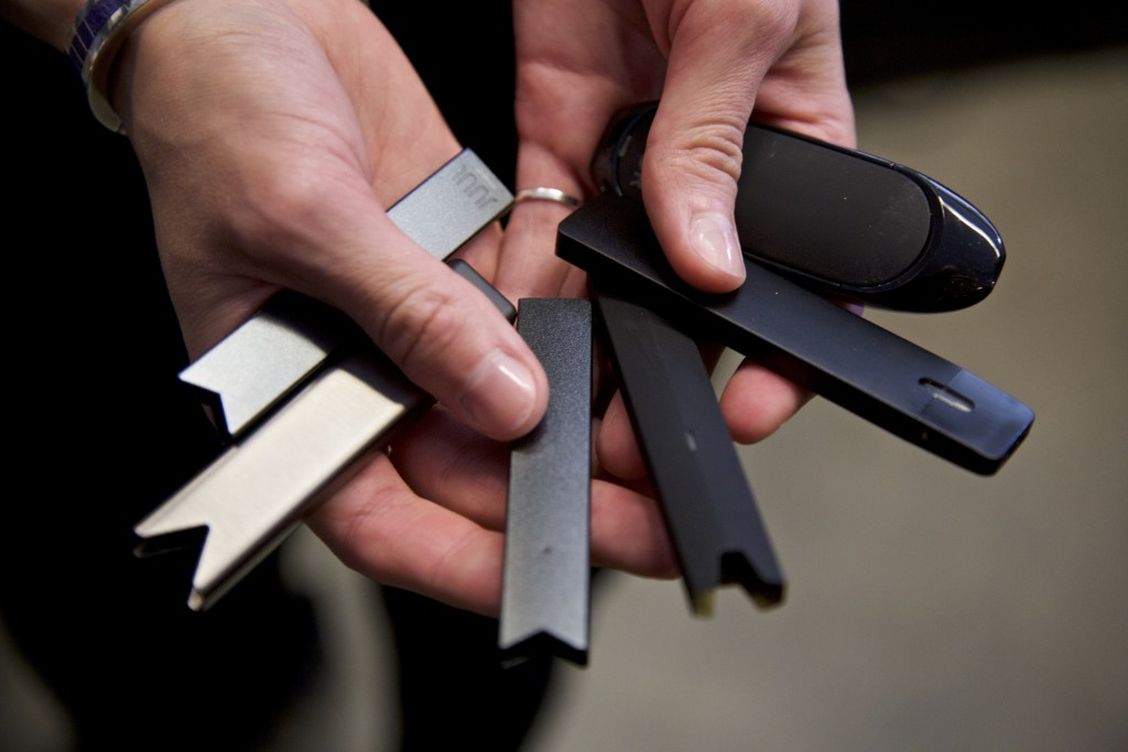 FILE - In this April 16, 2019, file photo, a researcher holds vape pens in a lab at Portland State University in in Portland, Ore. As of October 2019,...