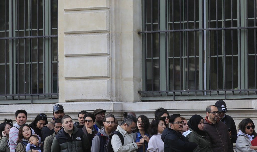 People line up outside the police headquarters in Paris, Friday, Oct. 4, 2019. The French government says there is nothing to suggest the police emplo...