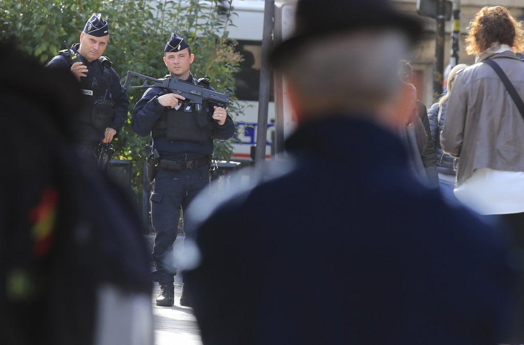 Police officers patrol outside the police headquarters in Paris, Friday, Oct. 4, 2019. The French government says there is nothing to suggest the poli