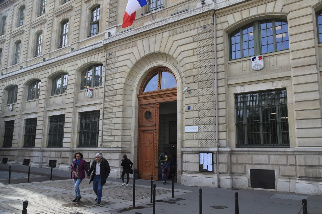 People walk out the police headquarters in Paris, Friday, Oct. 4, 2019. The French government says there is nothing to suggest the police employee who
