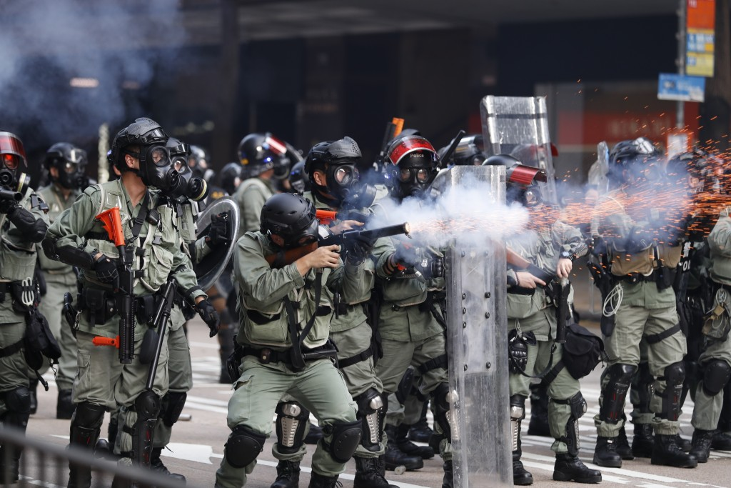 In this Tuesday, Oct. 1, 2019, file photo, police fire tear gas to disperse anti-government protesters in Hong Kong. Thousands of black-clad protester...