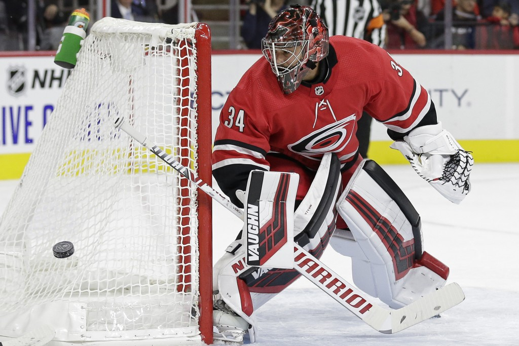 Carolina Hurricanes goaltender Petr Mrazek deflects a shot during the first period of the team's NHL hockey game against the Montreal Canadiens in Ral...