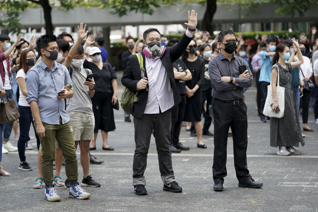 Protesters wear masks and hold up their hands represent the five demands in Hong Kong on Friday, Oct. 4, 2019. Hong Kong pro-democracy protesters marc