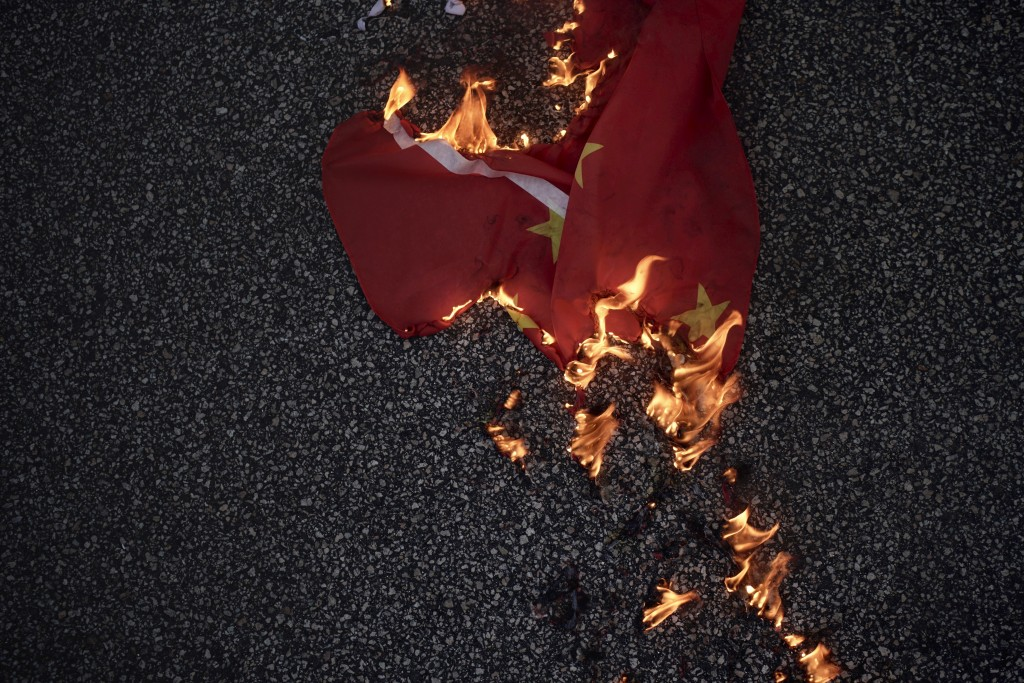 A Chinese national flag burns on the road in Hong Kong on Friday, Oct. 4, 2019. Thousands of protesters in masks are streaming into Hong Kong streets ...