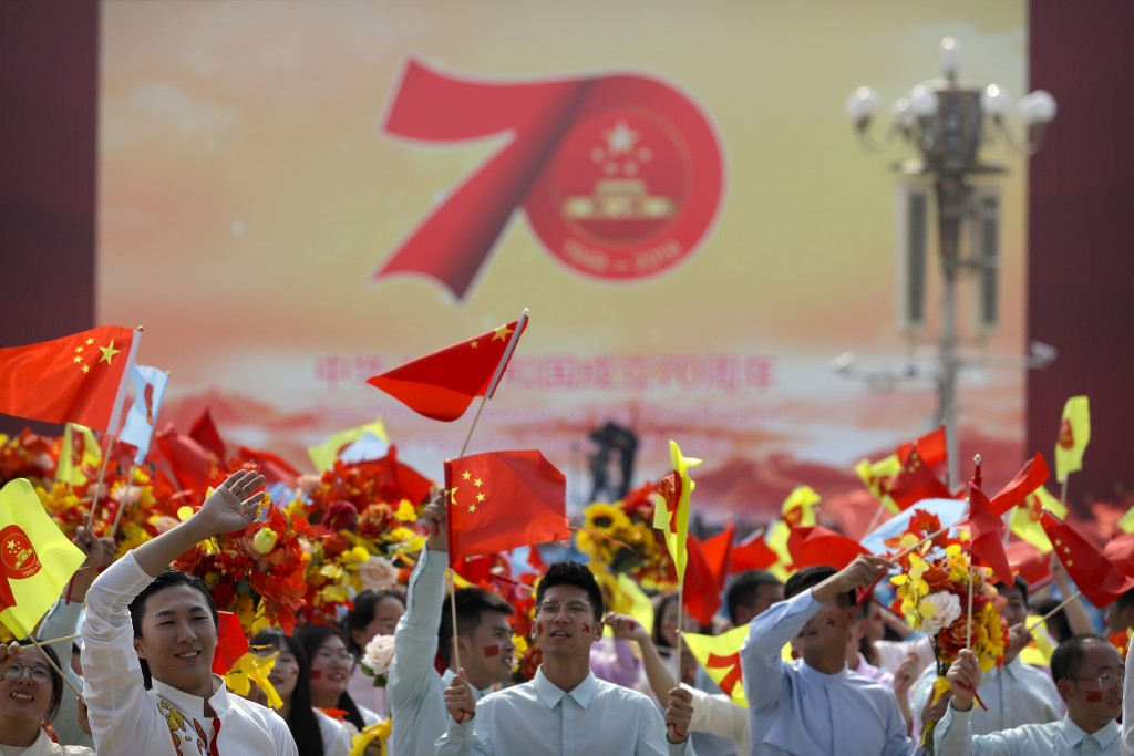 In this Tuesday, Oct. 1, 2019, file photo, participants wave flags during a parade to commemorate the 70th anniversary of the founding of Communist Ch...