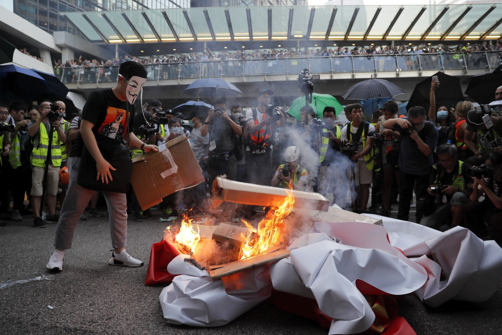 A masked protester sets fire to a China 70th anniversary celebration banner in Hong Kong, Friday, Oct. 4, 2019. Hong Kong Chief Executive Carrie Lam a