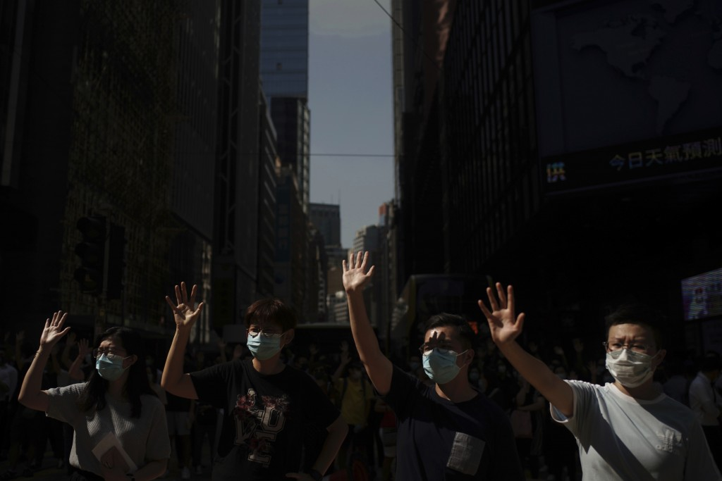 Pro-democracy protesters march in the city center ahead of reported plans by the city's embattled leader to deploy emergency powers to ban people from