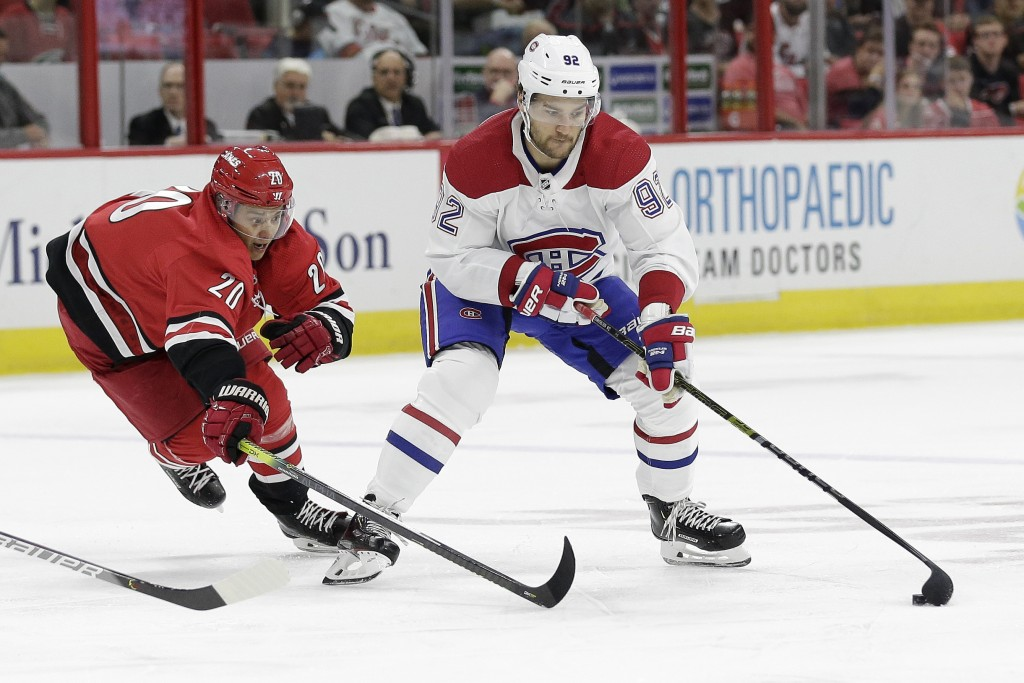 Carolina Hurricanes center Sebastian Aho (20), of Finland, reaches for the puck while Montreal Canadiens left wing Jonathan Drouin (92) skates during ...