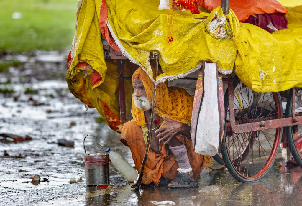 In this Saturday, Sept. 28, 2019, file photo, a Sadhu, or Hindu holy man, takes shelter from the rain under a cart in Prayagraj, in the northern India...