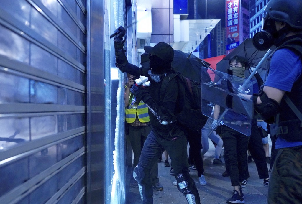 A protester damages a glass window on the streets of Hong Kong on Friday, Oct. 4, 2019. Masked protesters streamed into Hong Kong streets Friday after...