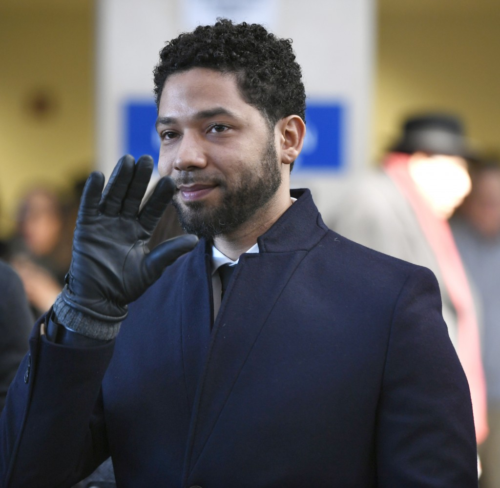FILE - In this March 26, 2019 file photo, actor Jussie Smollett smiles and waves to supporters before leaving Cook County Court after his charges were
