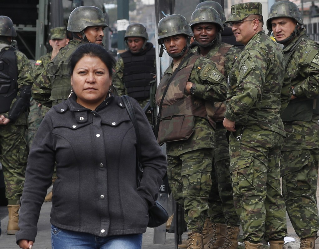Soldiers guarding an intersection watch as a woman crosses a street, after a night of rioting in Quito, Ecuador, Friday, Oct. 4, 2019. Ecuador's presi