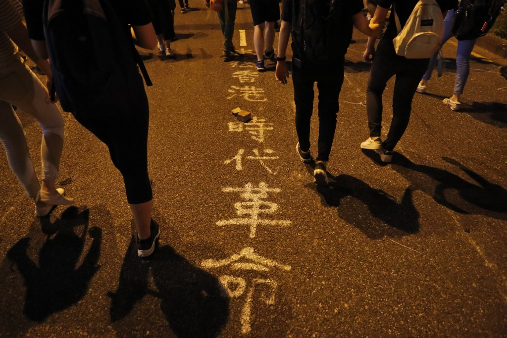 """Protesters walk past writing on a road that reads """"Hong Kong Era Revolution,"""" in Hong Kong Friday, Oct. 4, 2019. Thousands of defiant masked protester"""