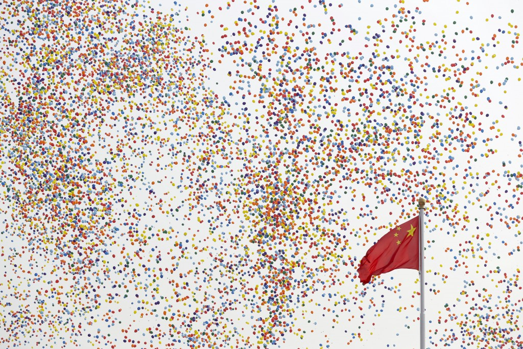 In this Tuesday, Oct. 1, 2019, file photo, balloons float past a Chinese flag on Tiananmen Square after being released during a parade commemorating t...