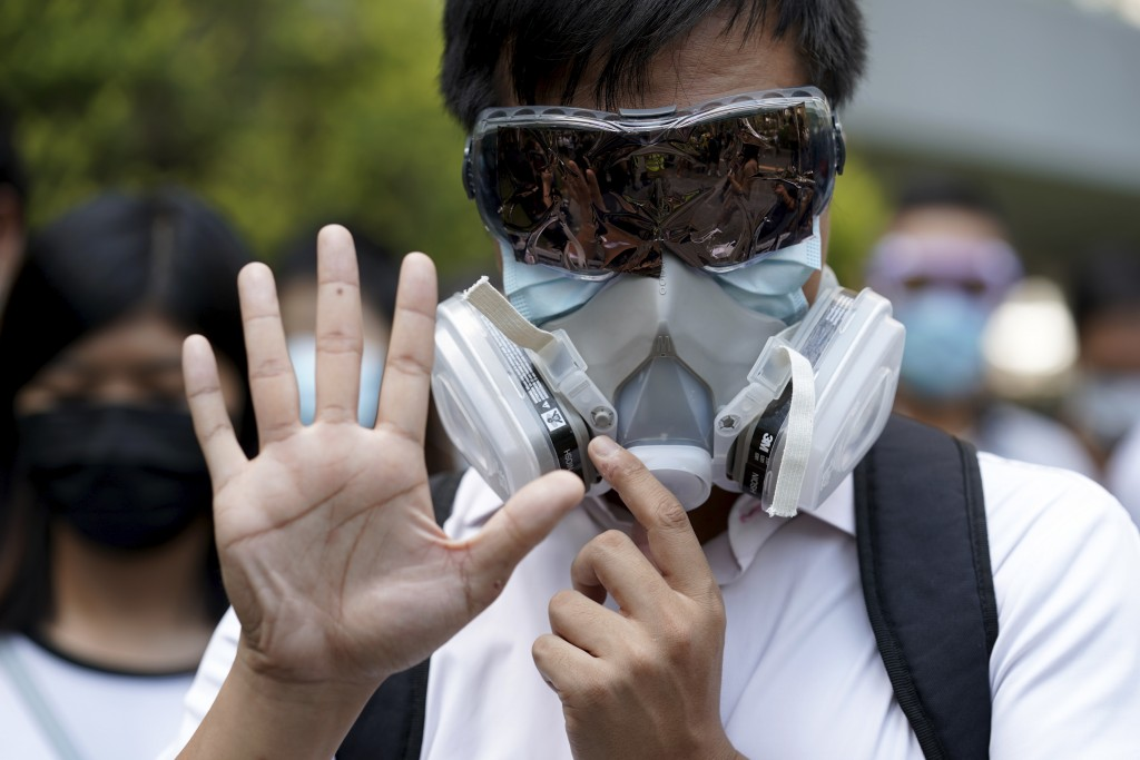 A protester wears a gas mask and holds up his hand to represent the protester's five demands in Hong Kong Friday, Oct. 4, 2019. Hong Kong pro-democrac