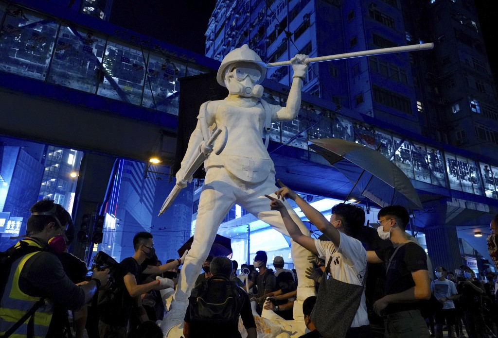 Protesters move a statue depicting a protester armed with gas mask, helmet and umbrella on the streets of Hong Kong on Friday, Oct. 4, 2019. Masked pr