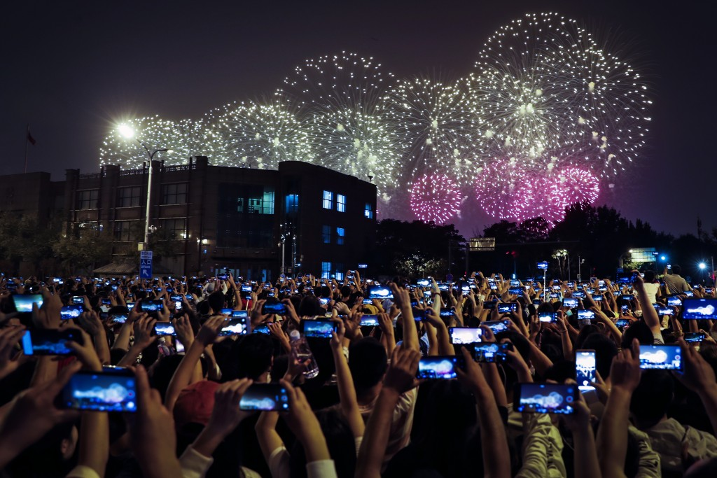 In this Tuesday, Oct. 1, 2019, file photo, people use smartphones to film fireworks exploding at Tiananmen Square as part of a gala evening commemorat...