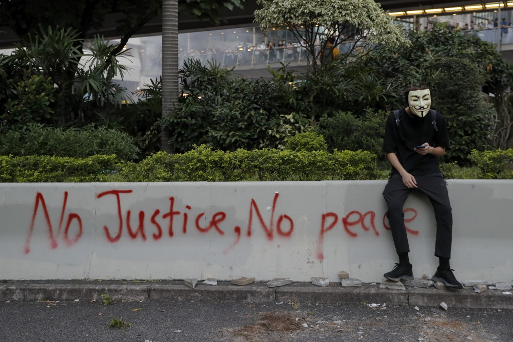 A masked protester sits near graffiti during a protest in Hong Kong, Friday, Oct. 4, 2019. Hong Kong Chief Executive Carrie Lam announced that protest...