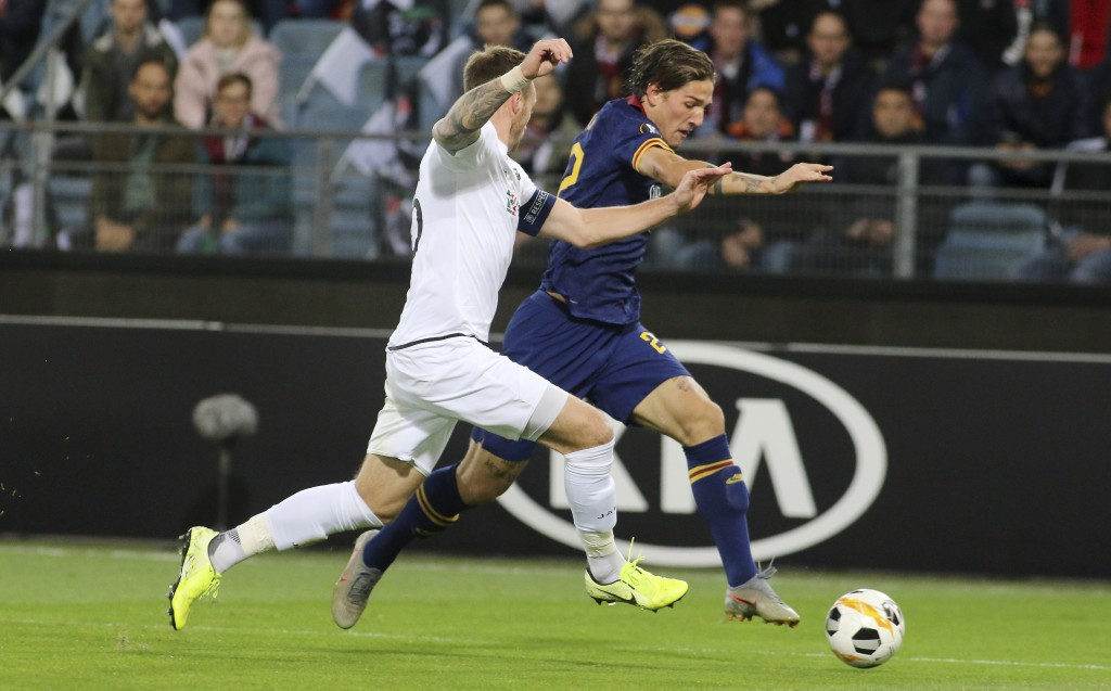 Wolfsberger's Michael Sollbauer, left, challenges for the ball with Roma's Nicolo Zaniolo during the Europa League group J soccer match between Wolfsb