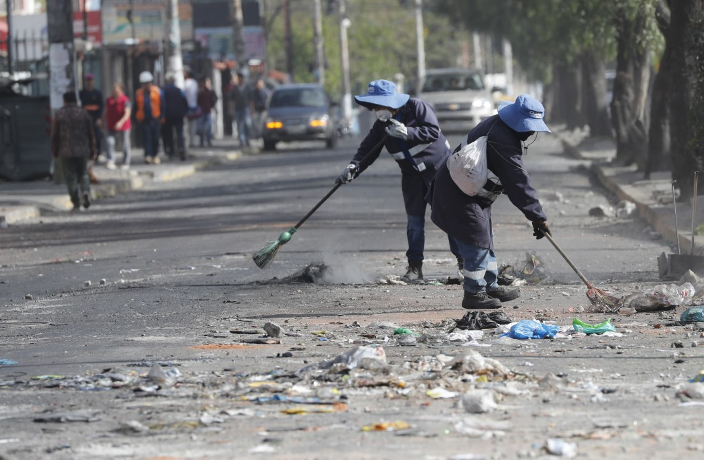 Municipal workers sweep debris off a street after a day of rioting in Quito, Ecuador, Friday, Oct. 4, 2019. Ecuador's president has declared a state o