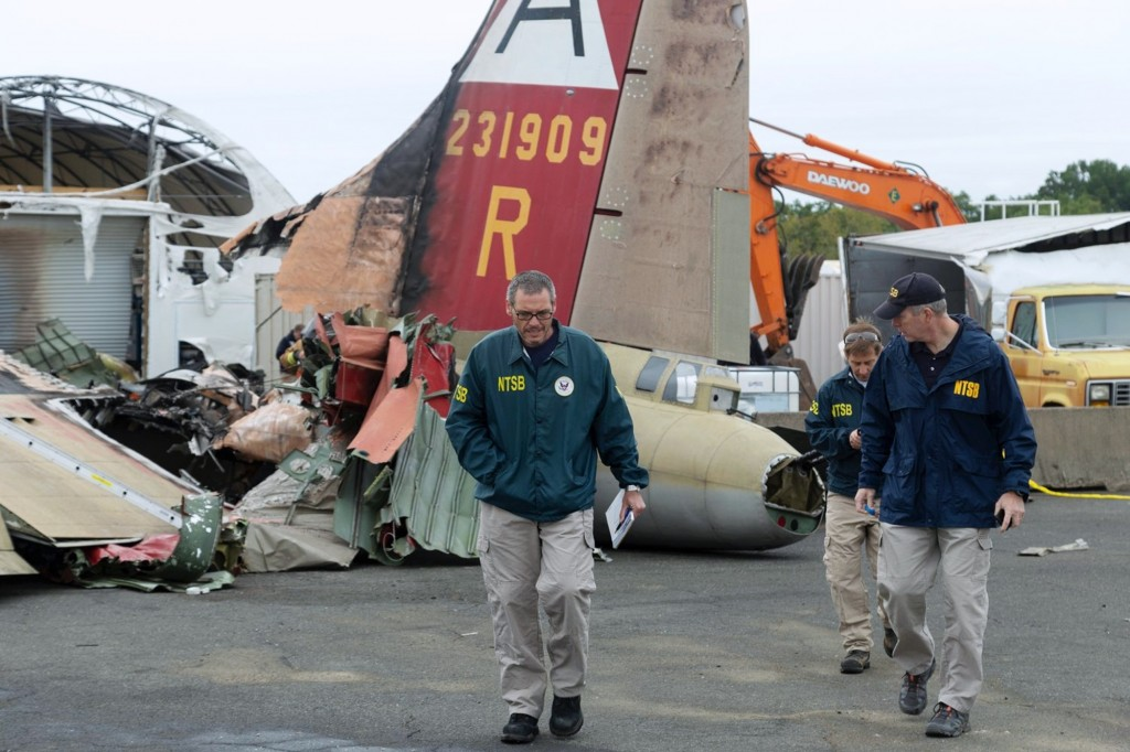 In this photo released via Twitter by the National Transportation Safety Board, NTSB investigator-in-charge Bob Gretz, left, walks Thursday, Oct. 3, 2...