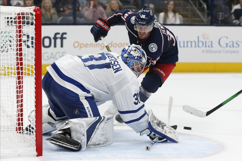 Toronto Maple Leafs' Frederik Andersen, front, of Denmark, makes a save against Columbus Blue Jackets' Boone Jenner during the second period of an NHL...