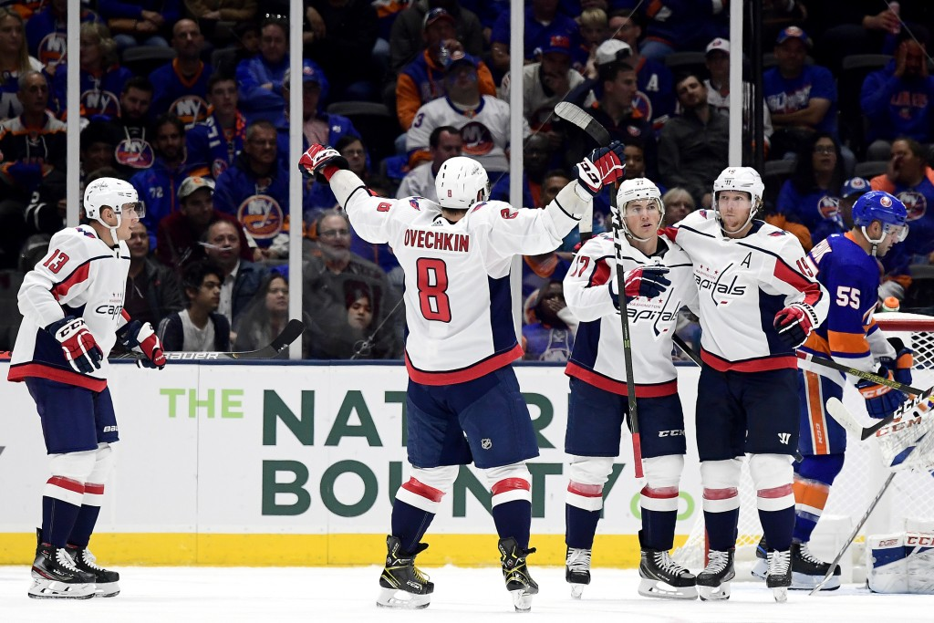 Washington Capitals right wing T.J. Oshie (77) is congratulated by teammates, including left wing Alex Ovechkin (8), center Nicklas Backstrom (19) and
