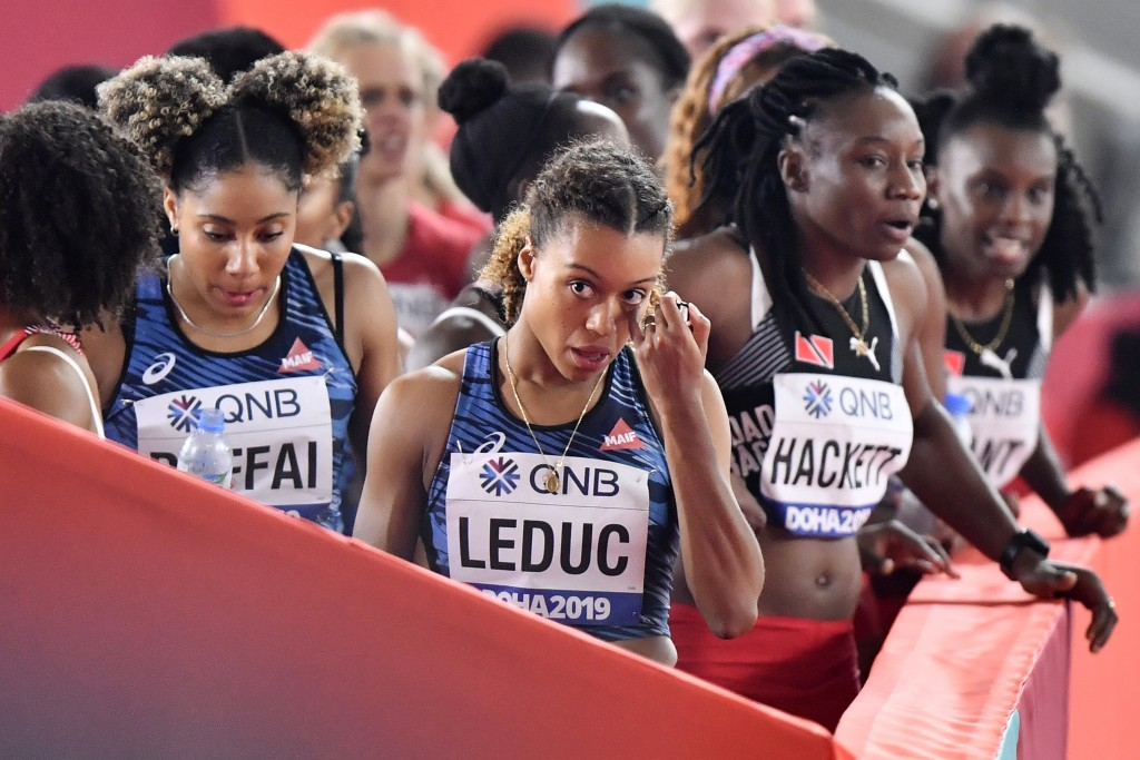 France's Cynthia Leduc, center, and Estelle Raffai, left, leave after their disqualification in the women's 4x100 meter relay at the World Athletics C...