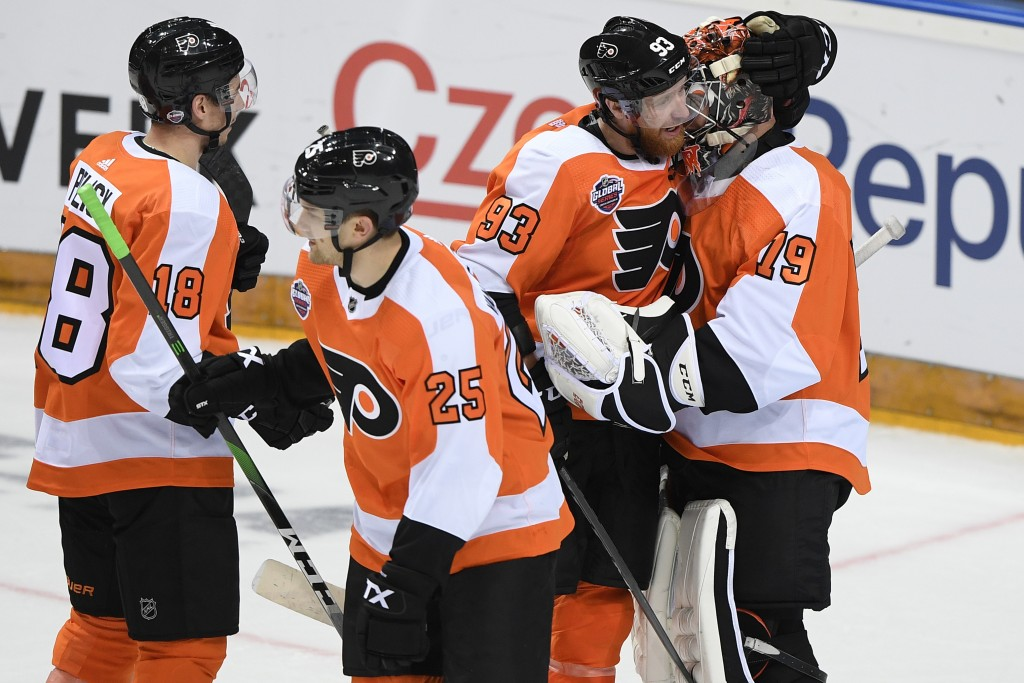 Philadelphia Flyers, from left, Tyler Pitlick, James van Riemsdyk, Jakub Voracek and Carter Hart, celebrate after they beat the Chicago Blackhawks 4-3