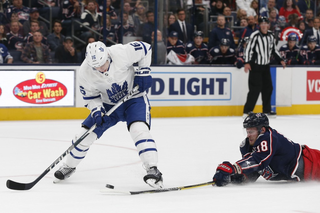 Columbus Blue Jackets' Pierre-Luc Dubois, right, knocks the puck away from Toronto Maple Leafs' Mitchell Marner during the first period of an NHL hock...