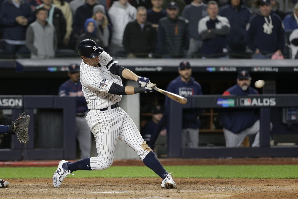 New York Yankees' DJ LeMahieu connects for a three-run double to left field against the Minnesota Twins during the seventh inning of Game 1 of an Amer...