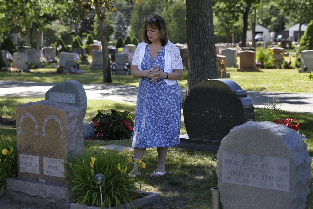 FILE - In this Tuesday, June 19, 2018 file photo, Cheryl Juaire, of Marlborough, Mass., stands at her son's grave, in Chelmsford, Mass. Victims of opi...