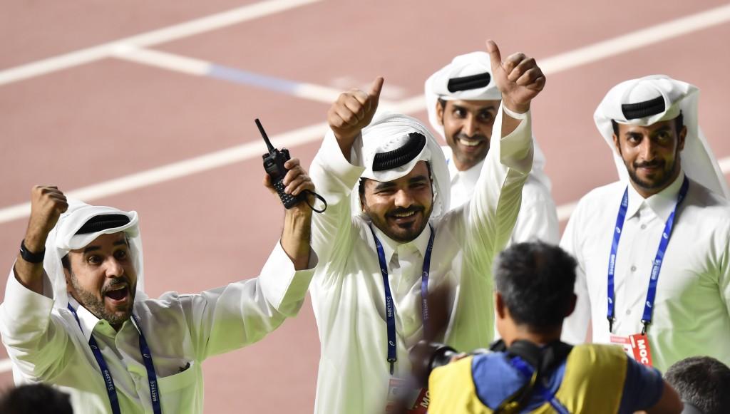 Sheikh Joaan bin Hamad bin Khalifa Al Thani, center, of Qatar, flashes two thumbs up when celebrating Mutaz Essa Barshim's gold medal in the men's hig...