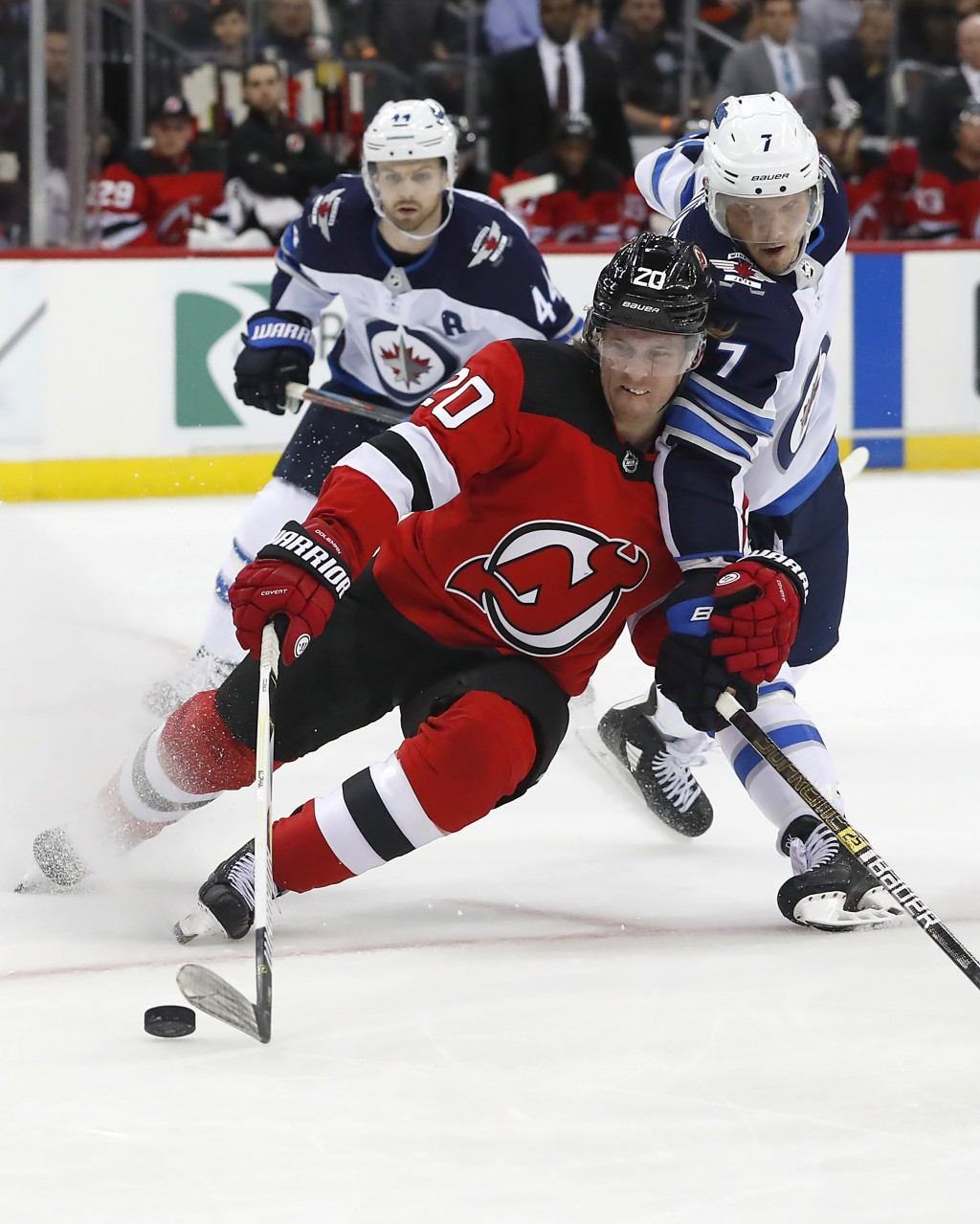New Jersey Devils center Blake Coleman (20) works against Winnipeg Jets defenseman Dmitry Kulikov (7) for the puck during the second period of an NHL ...