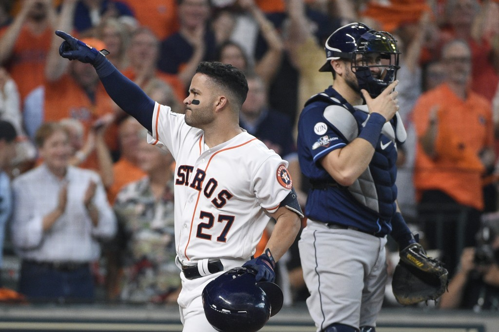 Houston Astros' Jose Altuve (27) celebrates after hitting a two-run home rung against the Tampa Bay Rays in the fifth inning during Game 1 in baseball...