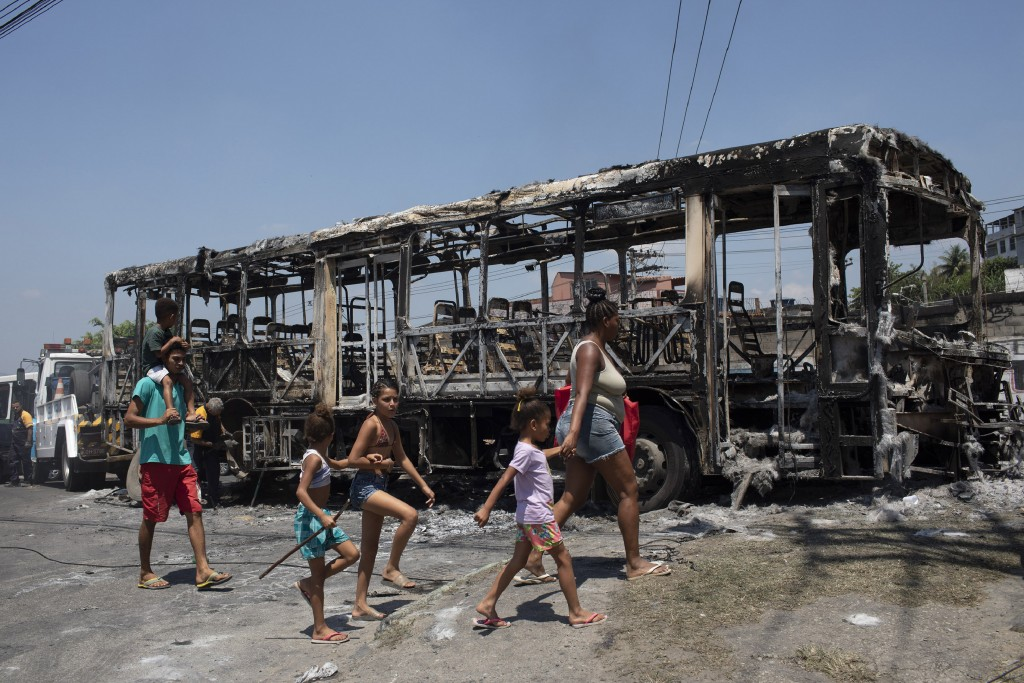 A family walks past the skeleton of a bus that was set on fire during overnight violent confrontations at the Costa Barros neighborhood of Rio de Jane...