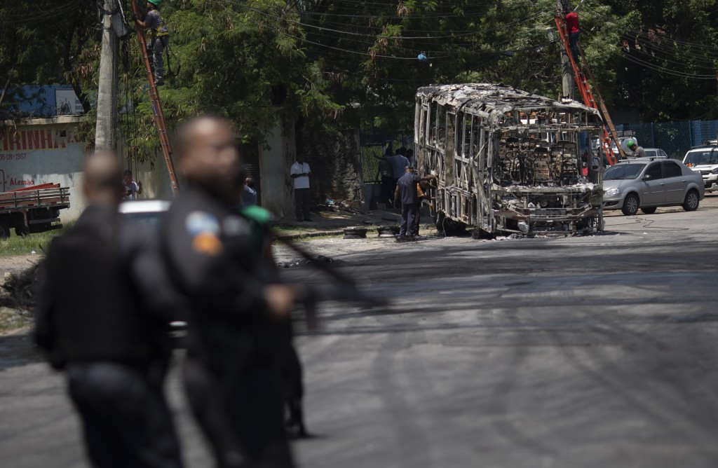 Police stand on a street close to the skeleton of a bus that was set on fire during overnight violent confrontations at the Costa Barros neighborhood