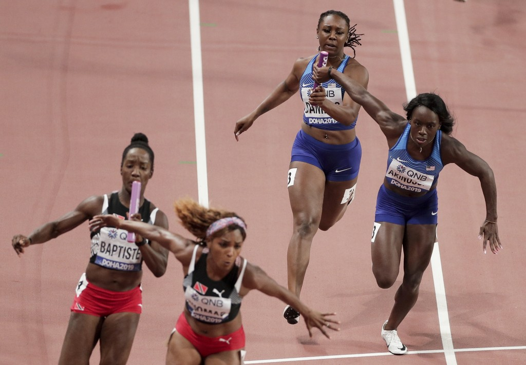 Teahna Daniels, right, of the United States hands off to Morolake Akinosun in the women's 4x100 meter relay semifinal at the World Athletics Champions