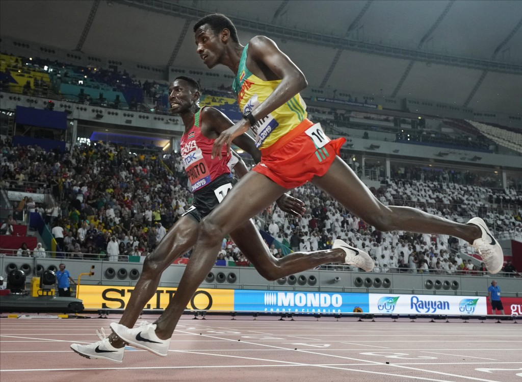 Conseslus Kipruto, left, of Kenya, wins ahead of Lamecha Girma, right, of Ethiopia, in the men's 3000 meter steeplechase final at the World Athletics