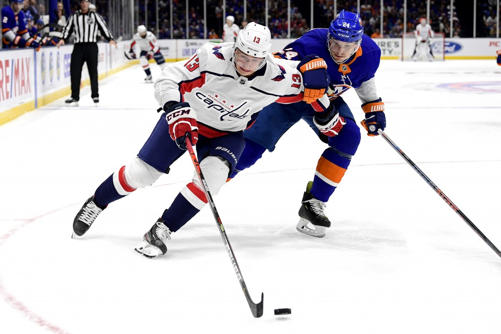 Washington Capitals left wing Jakub Vrana (13) and New York Islanders defenseman Scott Mayfield (24) chase down the puck during the first period of an