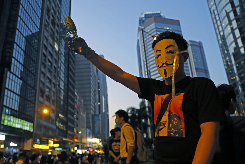 A protester wears a mask and holds up his hand as he occupied a road in Hong Kong Friday, Oct. 4, 2019. Hong Kong pro-democracy protesters marched in ...