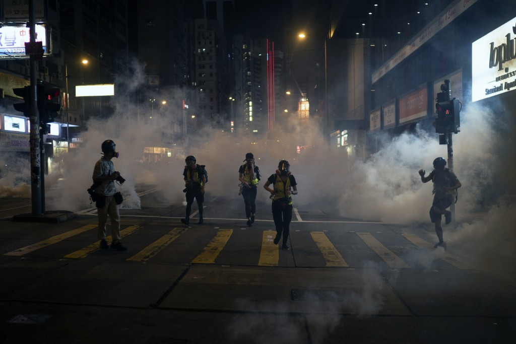 Emergency responders and journalists run from tear gas during a protest in Hong Kong on Friday, Oct. 4, 2019. Masked protesters streamed into Hong Kon